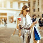 Female shopper on mobile phone holding coffee cup and bags